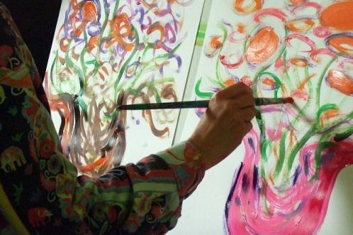 Cursist schildert twee schilderijen tegelijk, thema bloemen